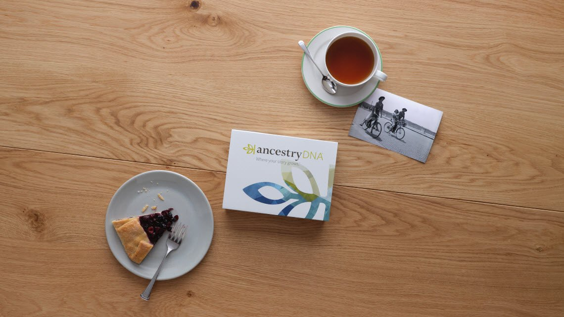 A cup of tea, a black and white image, and ancestry DNA kit and a piece of pie laying on a table