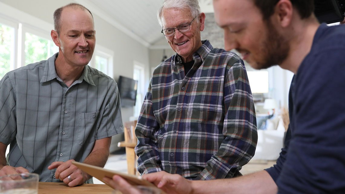 Three smiling men looking at table