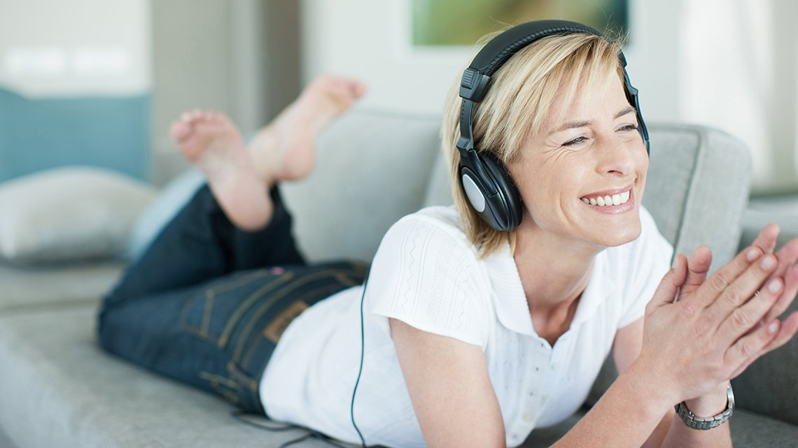 Smiling woman on couch listening to headphones