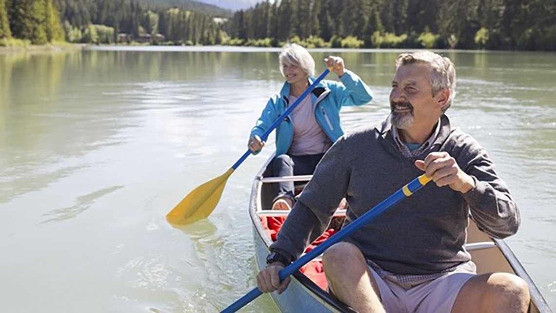 Man, woman paddling canoe on lake