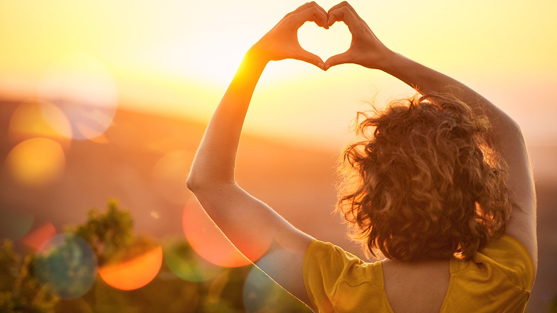 Rearview shot of an unidentifiable woman making a heart shape with her hands over a sunset landscape