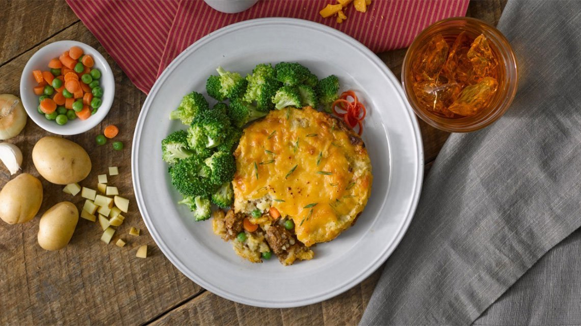 Un plato de pasta con queso, tomate y vegetales