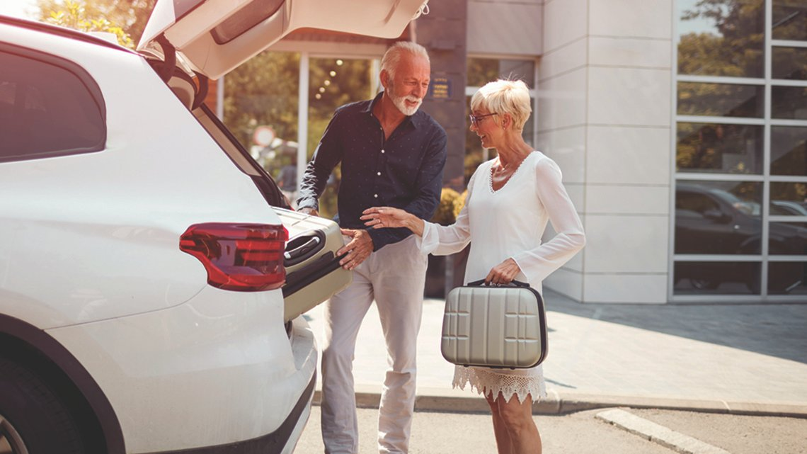 Mature man, woman loading suitcases into back white hatchback