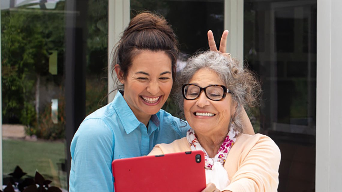 older and younger woman taking selfie