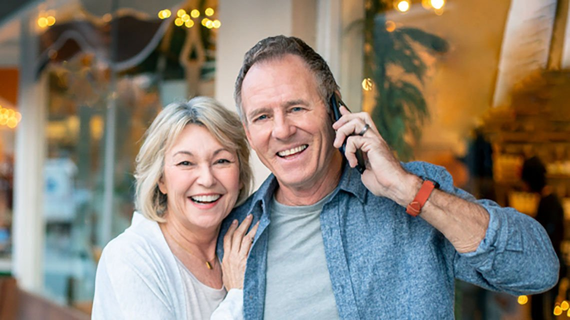 mature couple embracing outside, man with phone