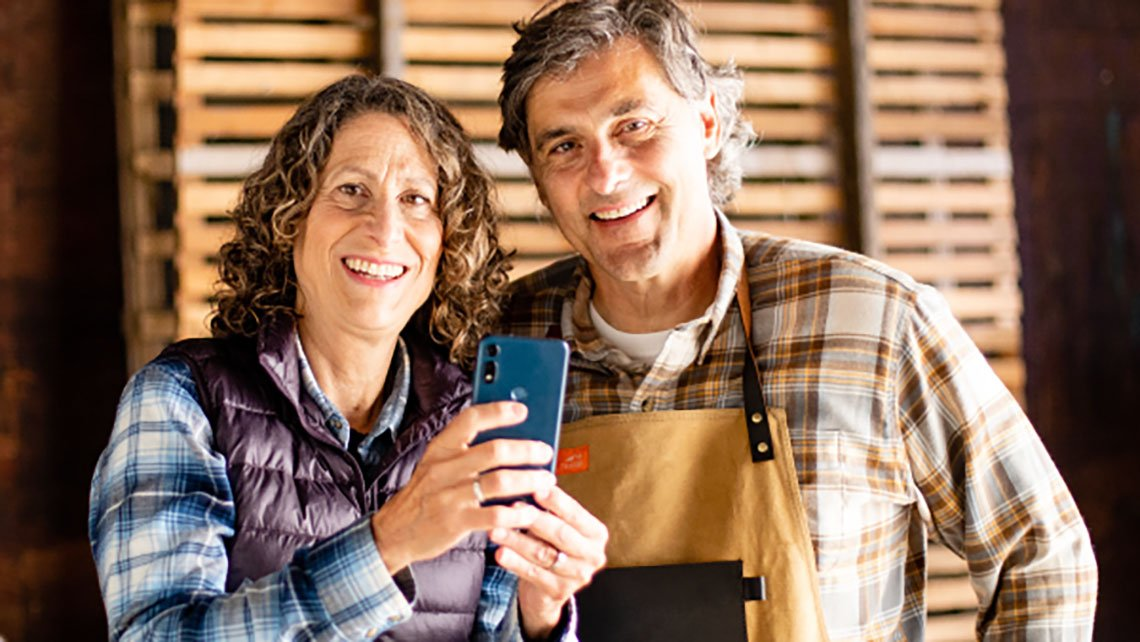 couple smiling holding a phone