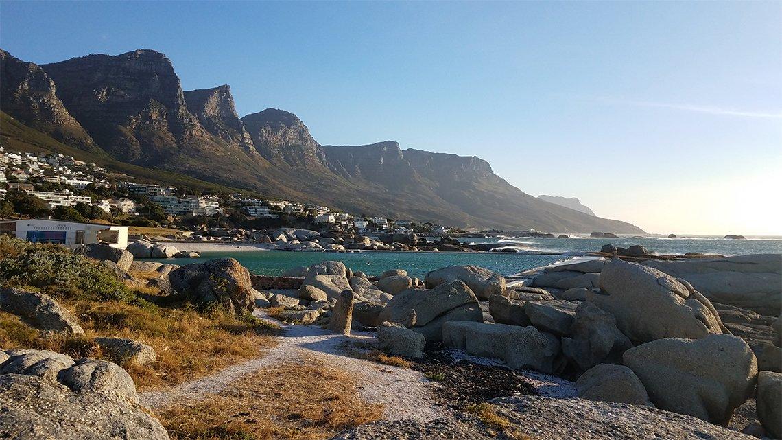 Shoreline: rocks, shrubbery, hills; buildings one side