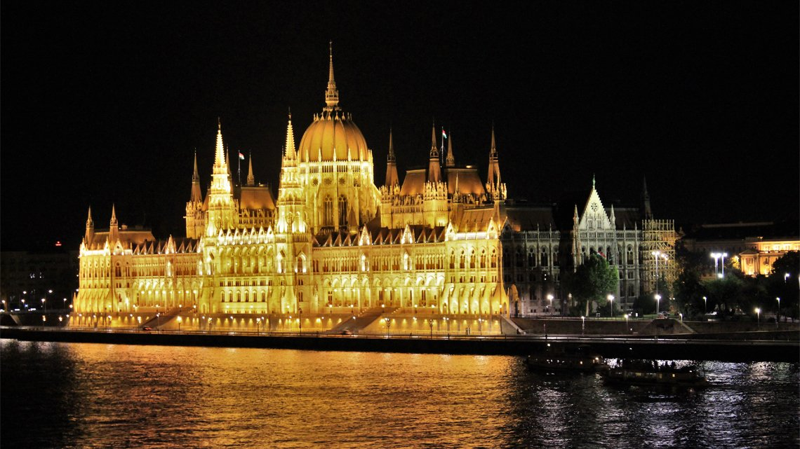 Danube river in front of building with dome, spires, lit up at night
