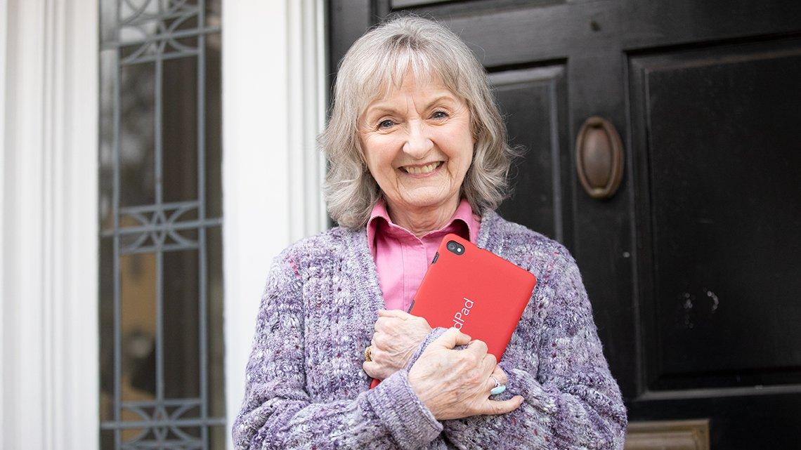Mature woman holding red grandpad