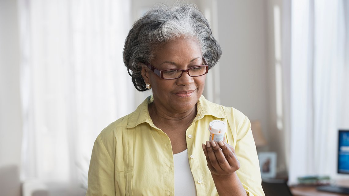 Mature African American woman holding prescription bottle