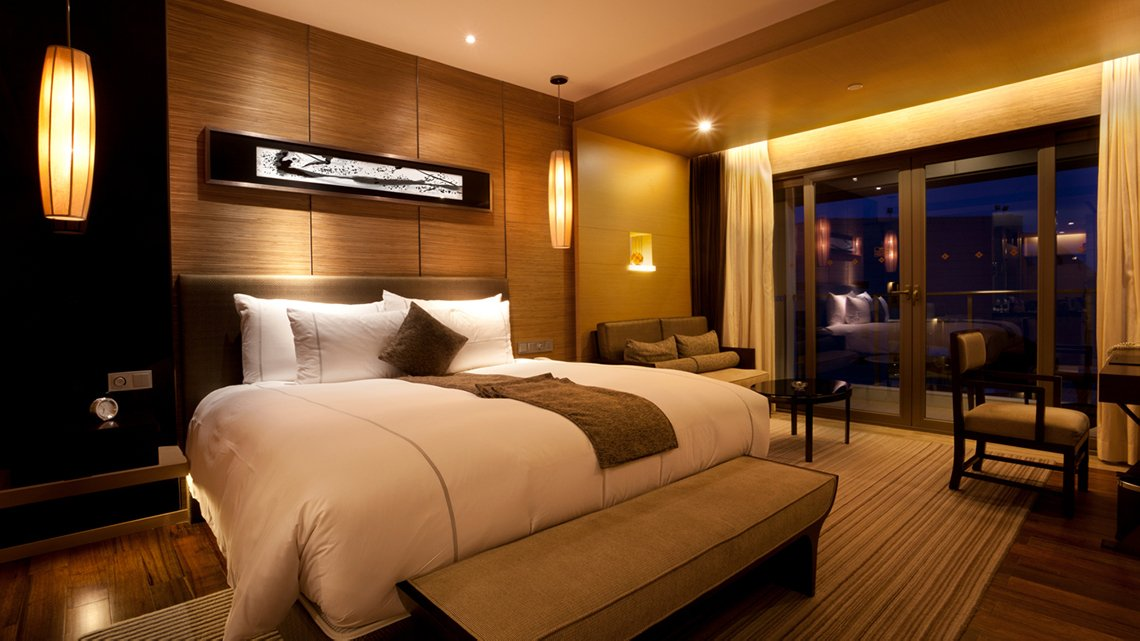 Hotel room, king bed in front of bamboo slat covered wall, gold colored lighting, glass doors