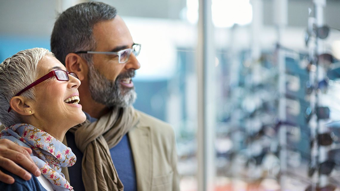Closeup side view of a late 40's couple standing in front of eyeglasses store and making a choice for buying a new pair each. They are amazed with the selection offered and can't make up their mind.