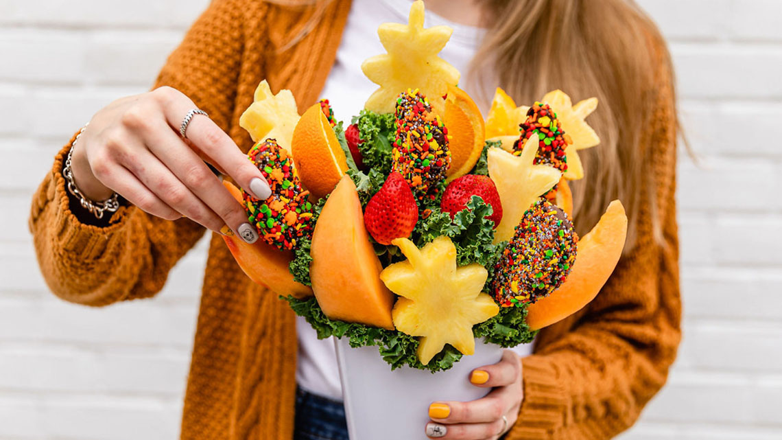 woman holding a fall themed fruits assortment