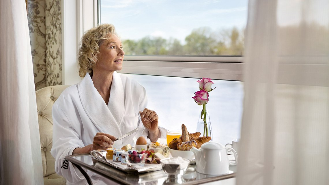 Woman sitting looking out window, river view, at table with breakfast