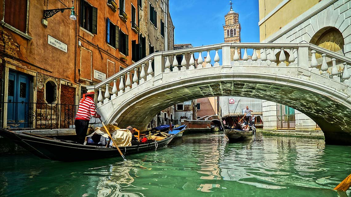 People in two gondolas passing each other under bridge