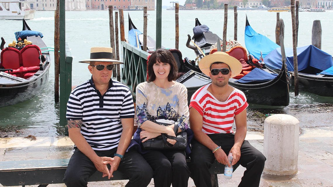 Woman sitting between 2 gondoliers in front of gondolas on canal