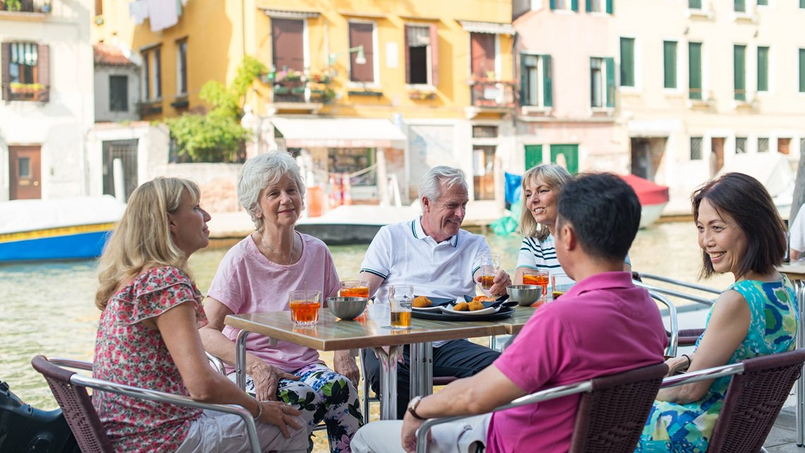 Six people around table with food, drinks, near a canal across from buildings