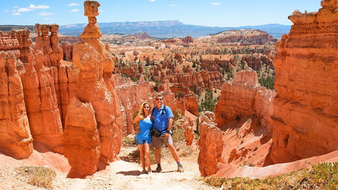Smiling couple embracing on trail in the red mountains, Bryce Canyon National Park, Utah