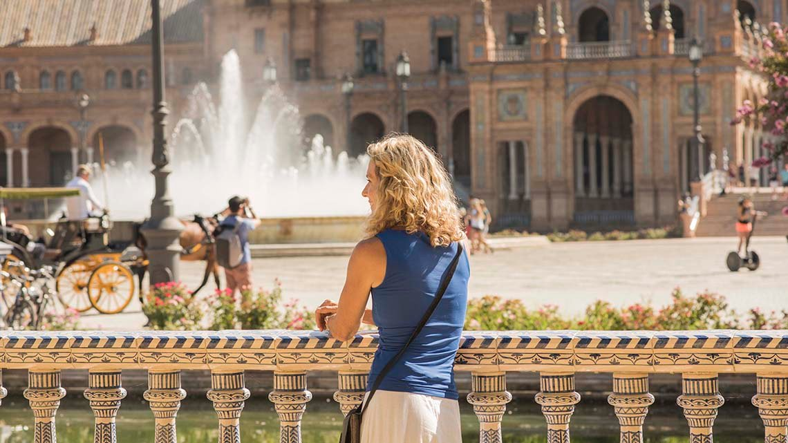 Blonde woman leaning on river railing across from plaza with fountain