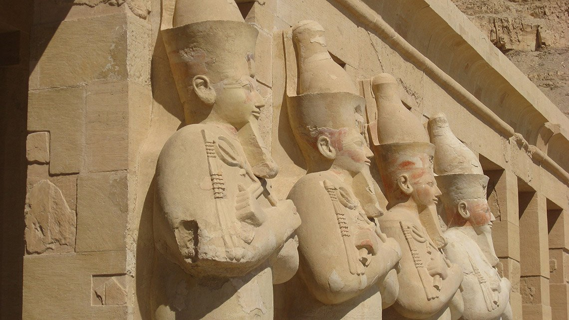 Frieze of four male Egyptian rulers with beards, arms crossed
