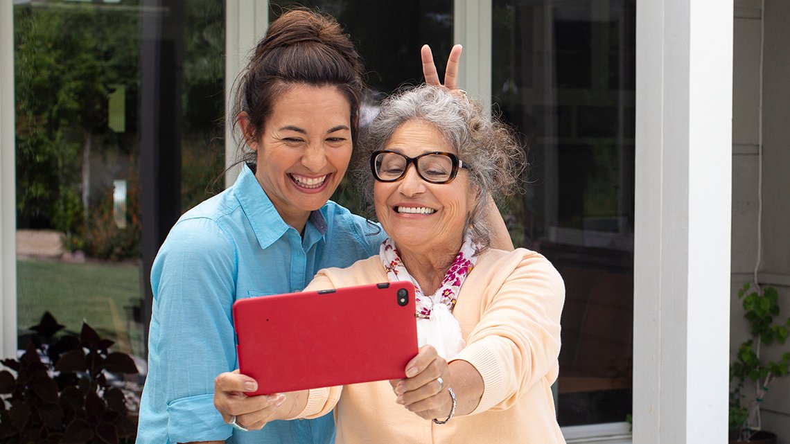 older and younger woman taking selfie with grandpad