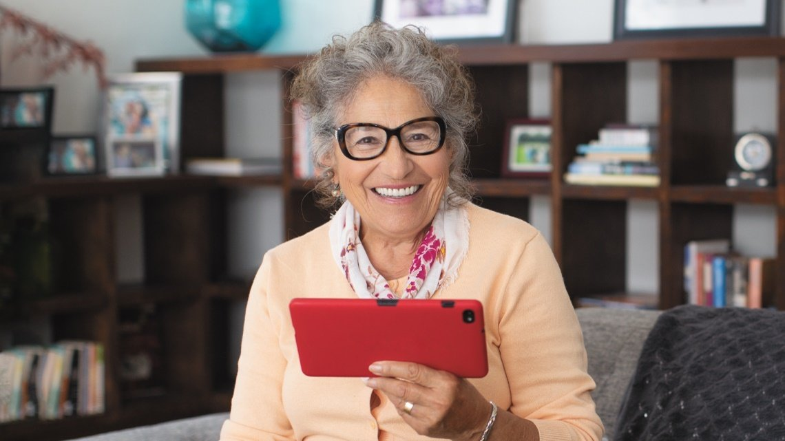 Smiling senior woman, red tablet
