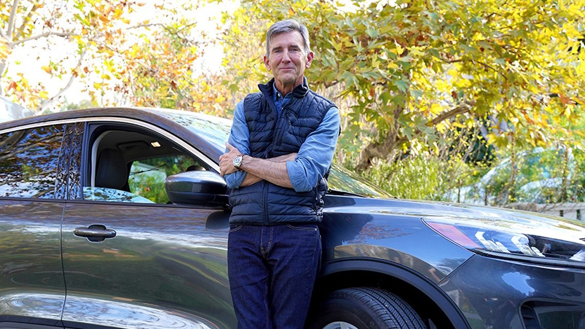 Man leaning against blue car