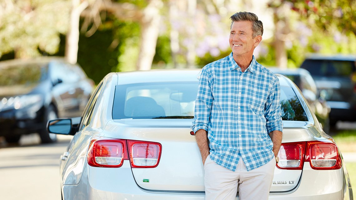 Man standing in front of car smiling with hands in pocket