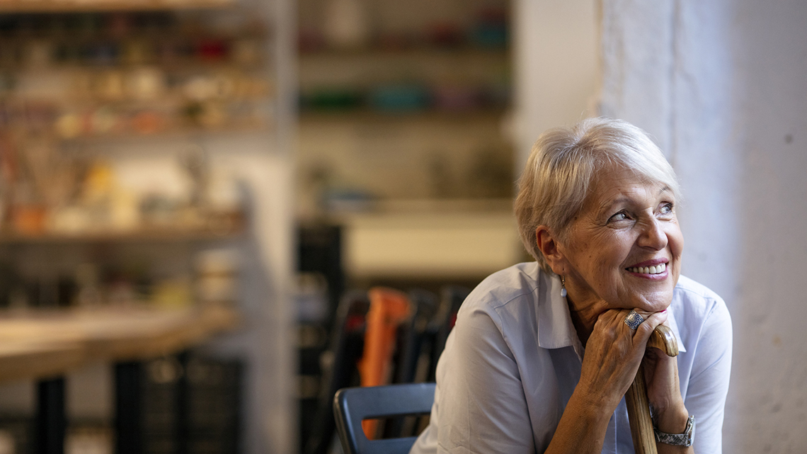 Happy Senior woman sitting and looking out the window while leaning on walking stick during the day.