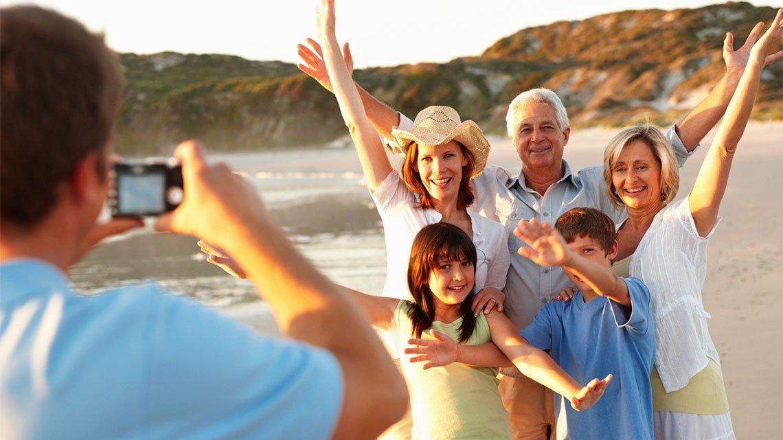 Man taking photo of 3 generation family at beach beach, sunny day
