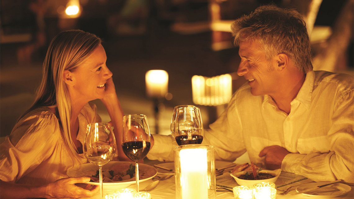 Couple dining, wine glasses, candles on table