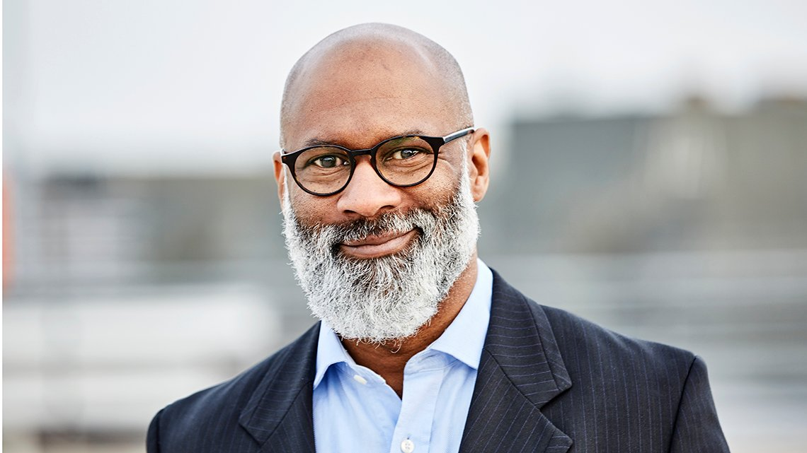 Mature, bearded, African American man with black frame glasses