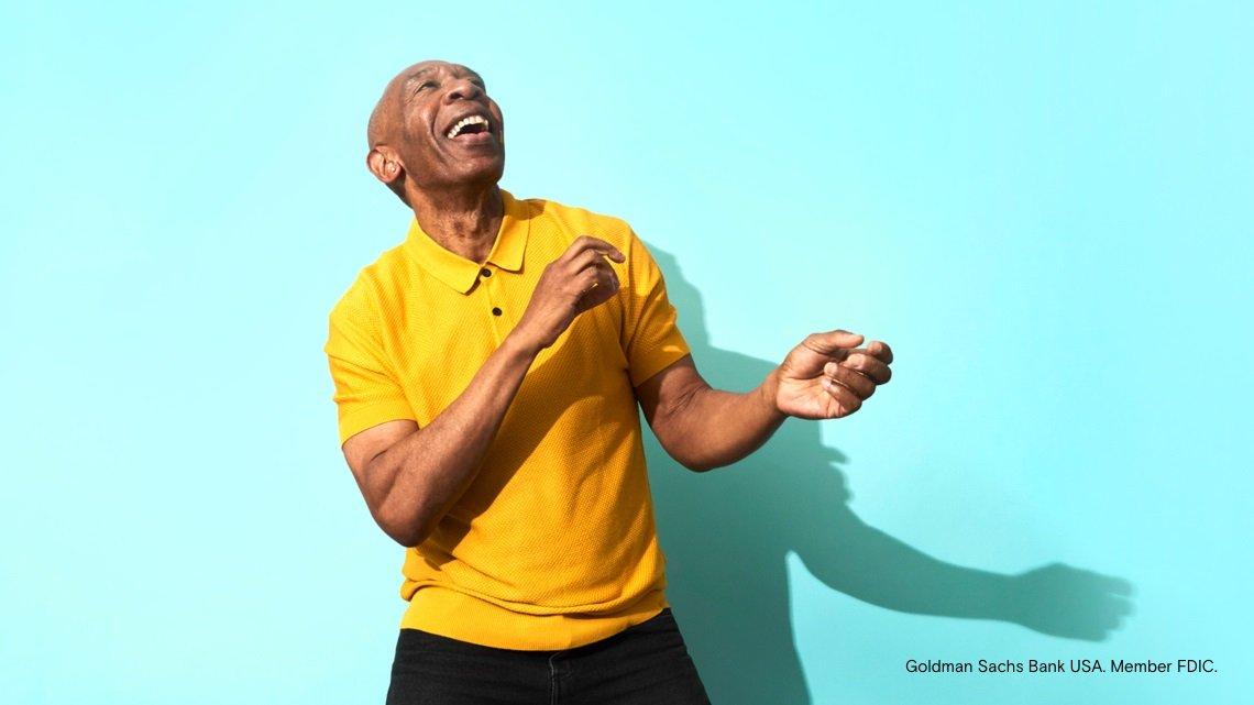 man dancing, yellow sweater, blue background