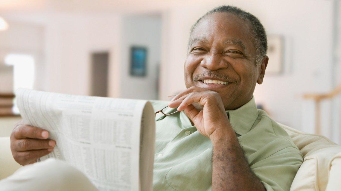 Smiling senior man newspaper glasses