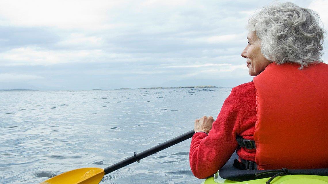 Woman, red life vest paddling kayak