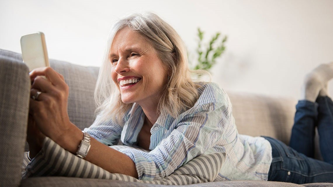 Smiling woman on couch with smartphone