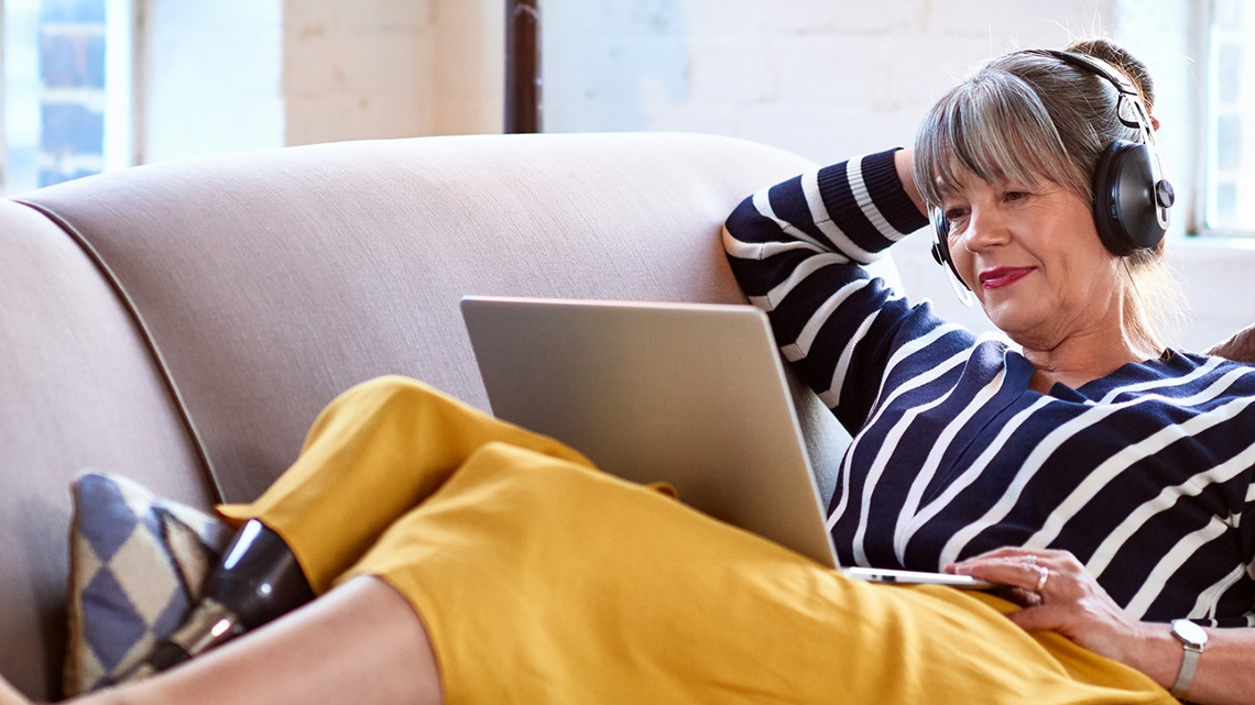 woman-on-couch-headphones-tablet-stiped-blouse-yellow-skirt