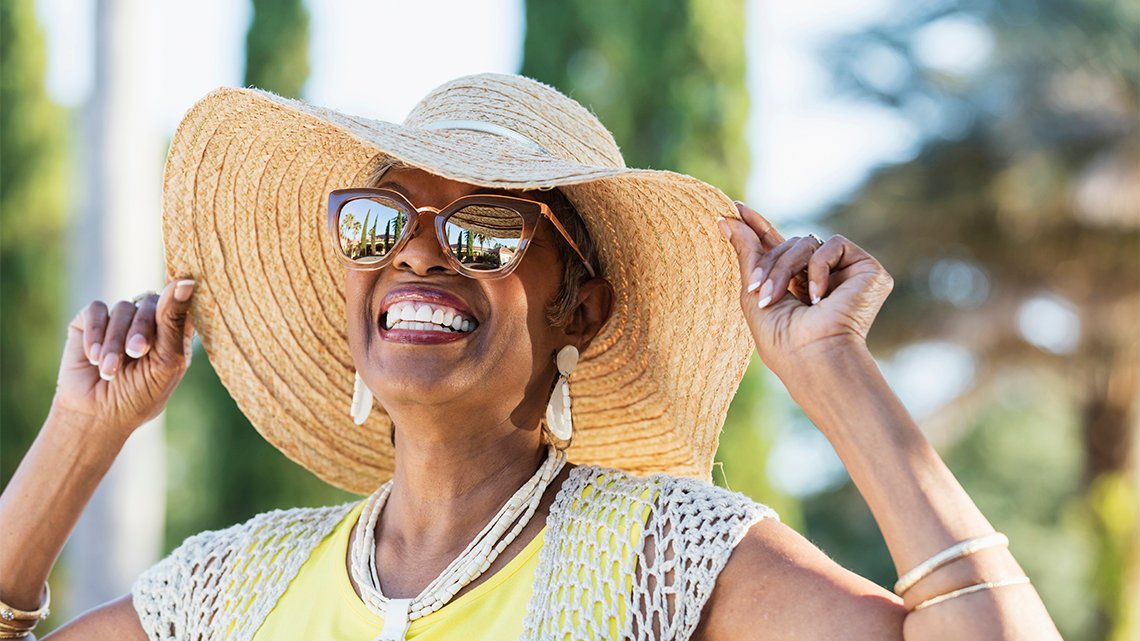 Smiling senior African-American woman, hat, sunglasses looking up at the sky