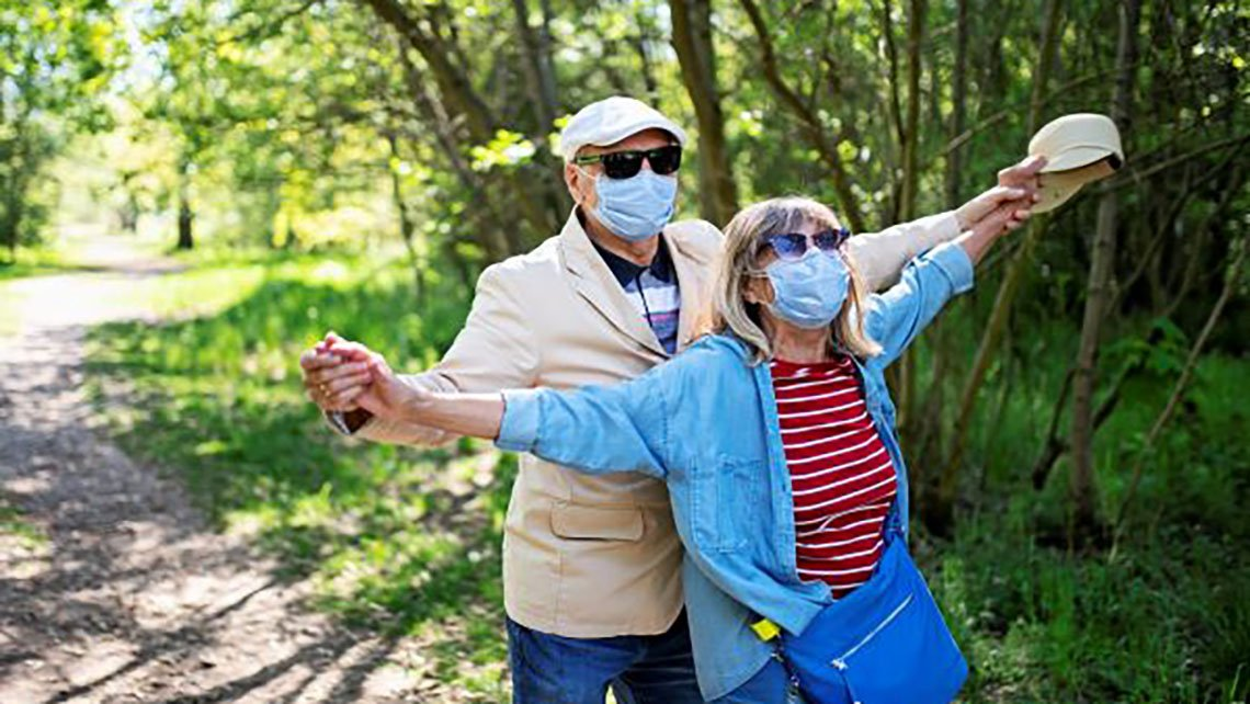 couple wearing masks hiking in the forest