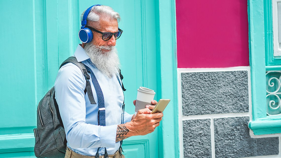 Trendy mature man drinking coffee and using music smartphone app in outdoor downtown area