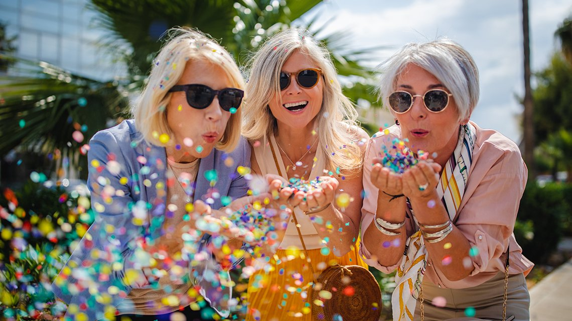 Three mature women, sunglasses, smiling, blowing colorful confetti on city street