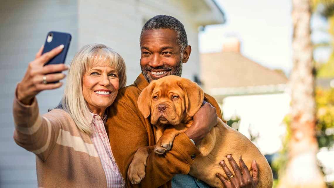 man holding dog, woman taking selfie