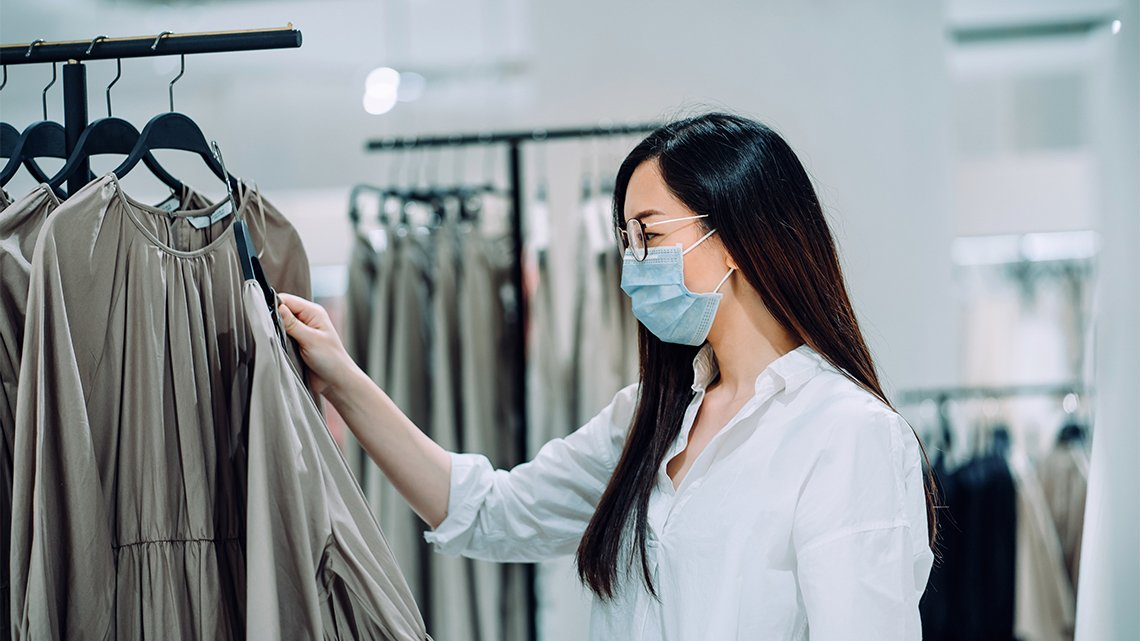Masked woman looking at dresses on rack