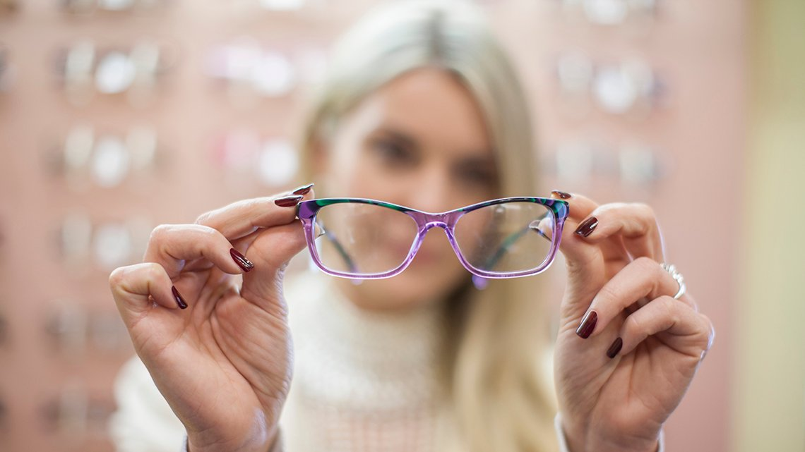 Woman looks through lens of glasses and tilts it slightly