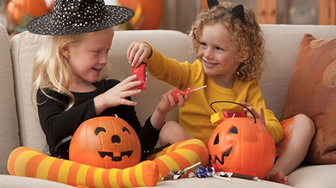 Two smiling little blonde girls trading Halloween candy