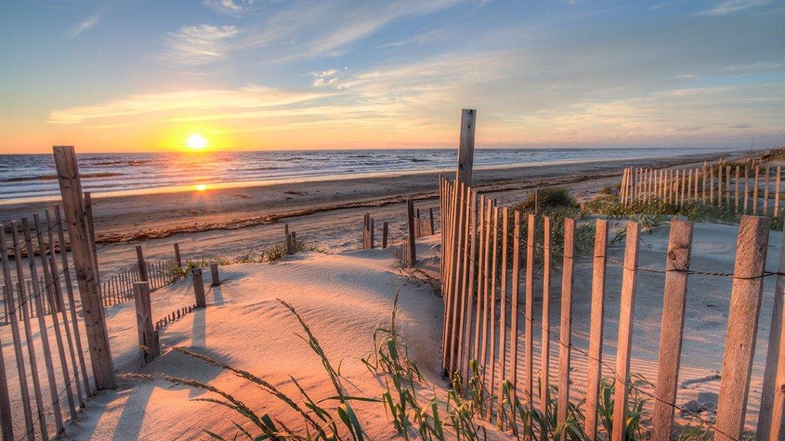 Sandy path, wood rail fence on sides, leading to beach, sun setting over ocean