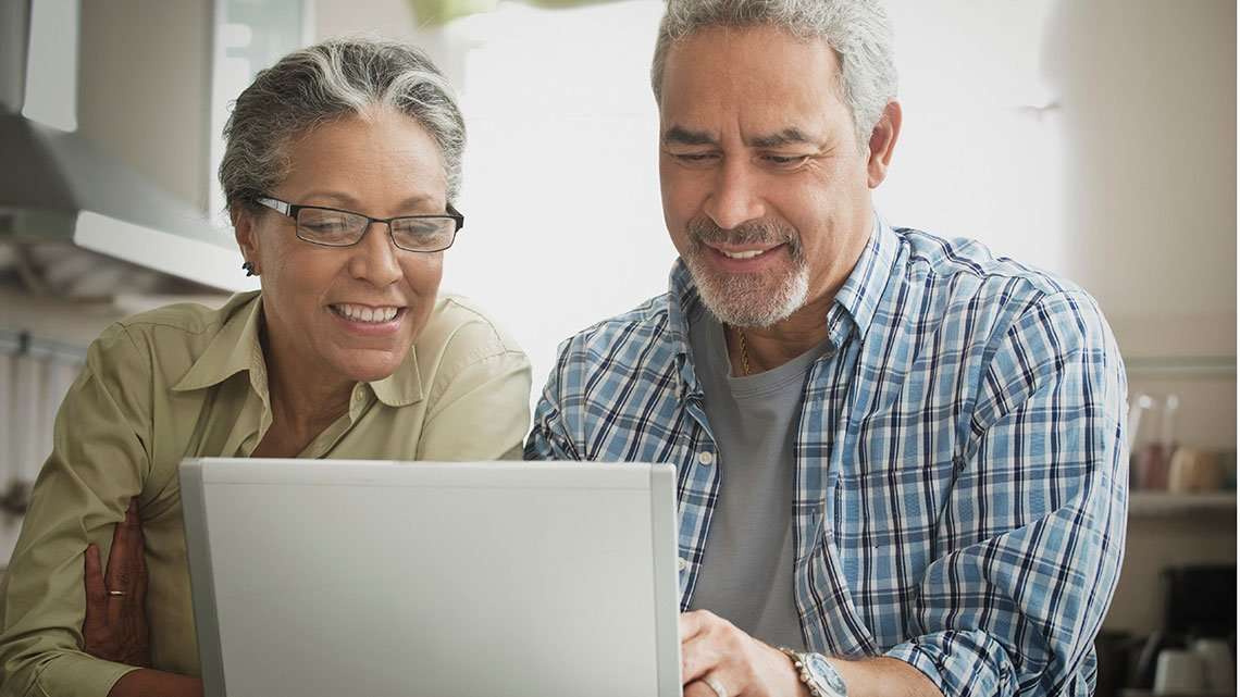 Smiling, mature Hispanic man, woman looking at laptop in kitchen
