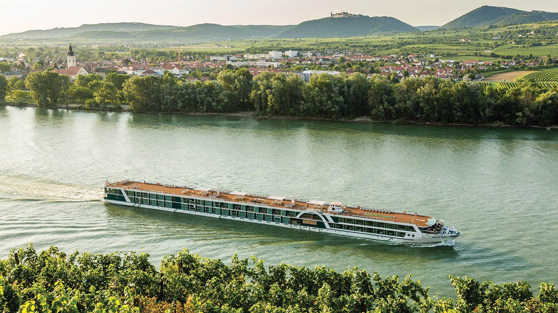 river cruise ship, wide river, tress, city