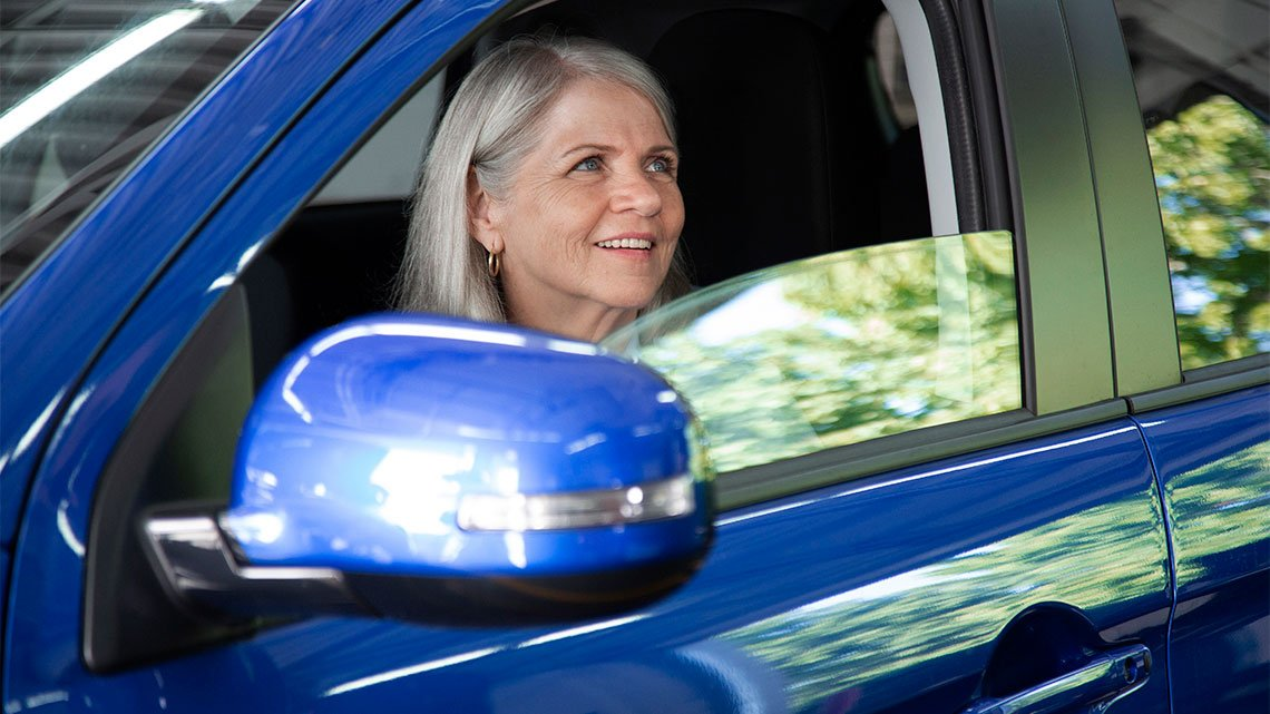 smiling woman blue car window open