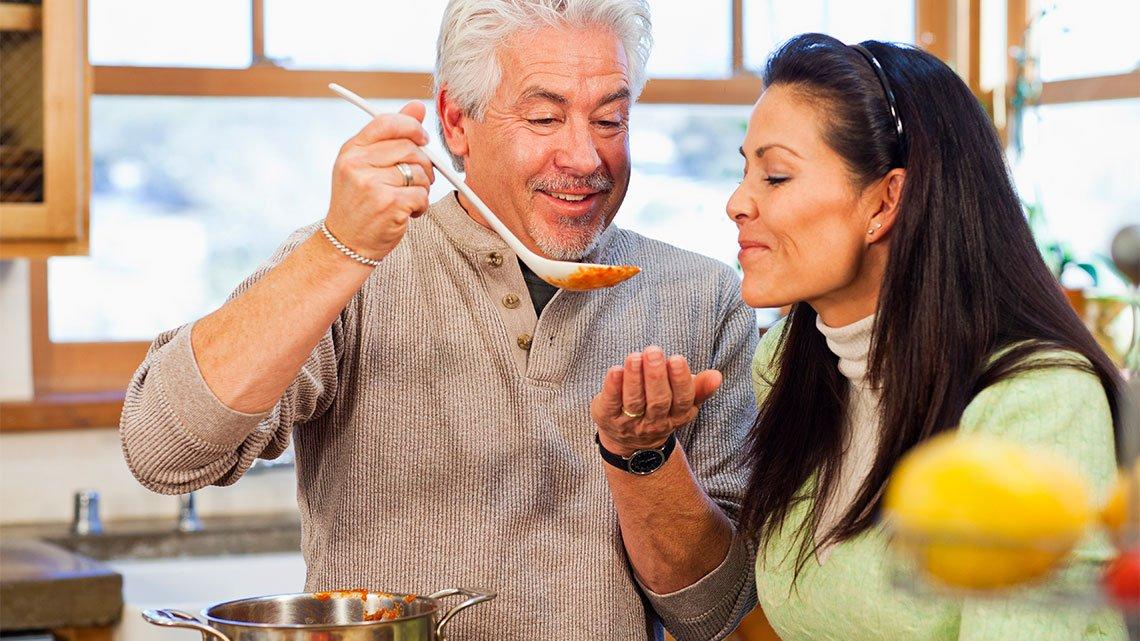 Hispanic couple tasting sauce